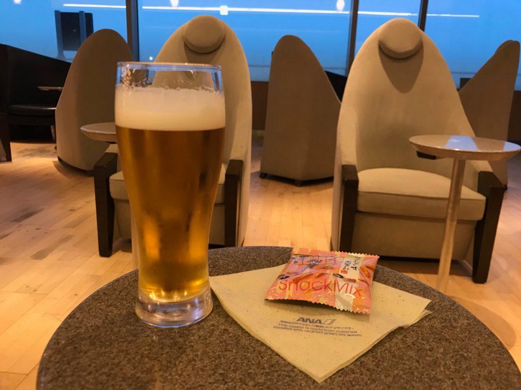 羽田空港国内線のANAラウンジでビールとおつまみを食べている写真です。